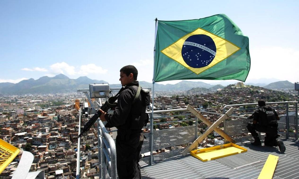Polícia Civil hasteia bandeira do Brasil no teleférico do Morro do Alemão Foto: Marcelo Piu / Agência O Globo - 28/11/2010