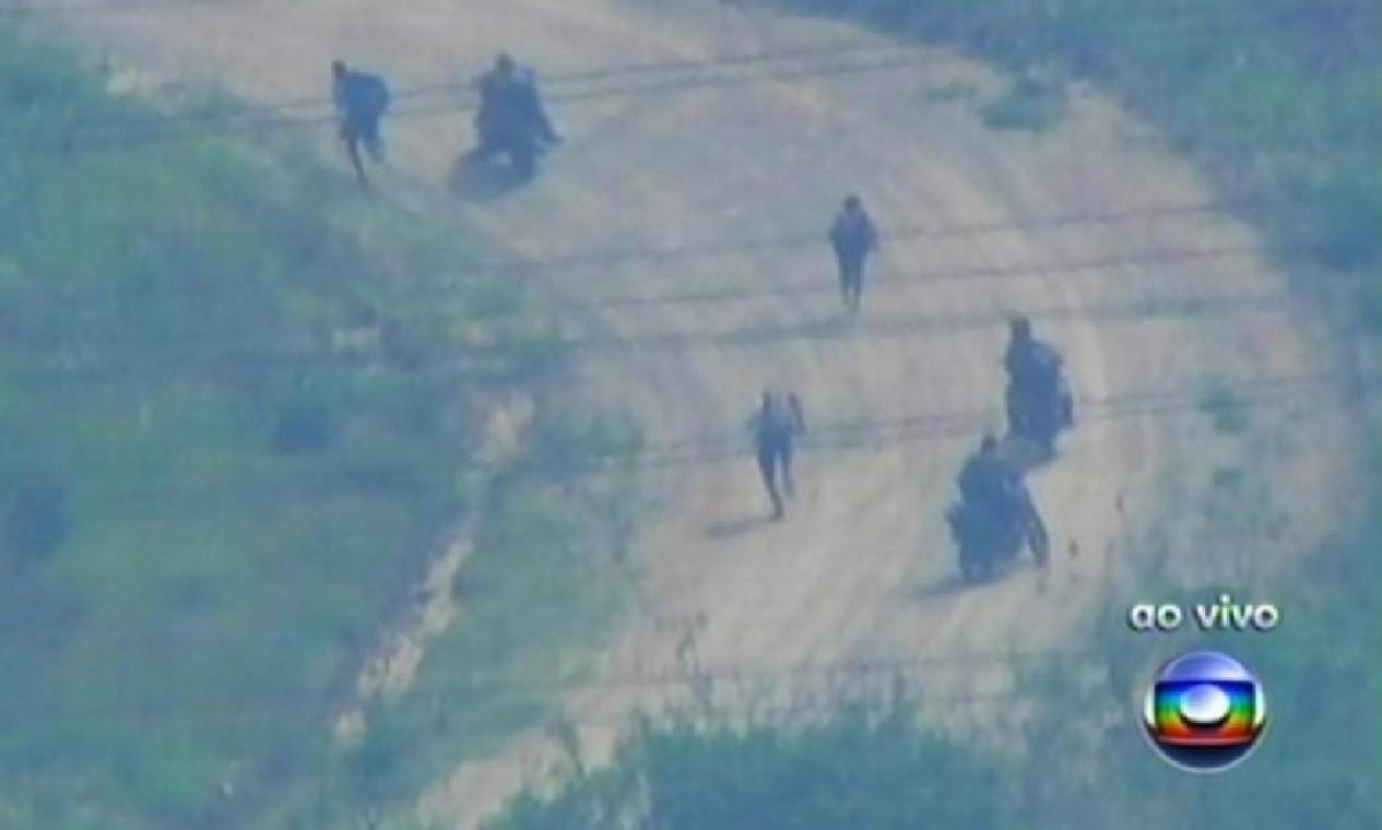 Uma das imagens mais marcantes da tomada do Complexo do Alemão: o flagrante do momento em que traficantes armados fugiram pela mata Foto: Reprodução / TV Globo
