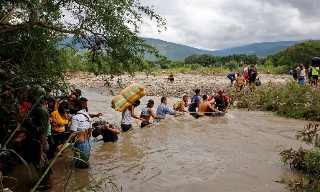 Migrantes usam uma corda para cruzar o rio Tachira, a fronteira natural, em Cúcuta, entre a Colômbia e a Venezuela, pois a fronteira oficial permanece fechada devido à pandemia COVID-19 Foto: SCHNEYDER MENDOZA / AFP