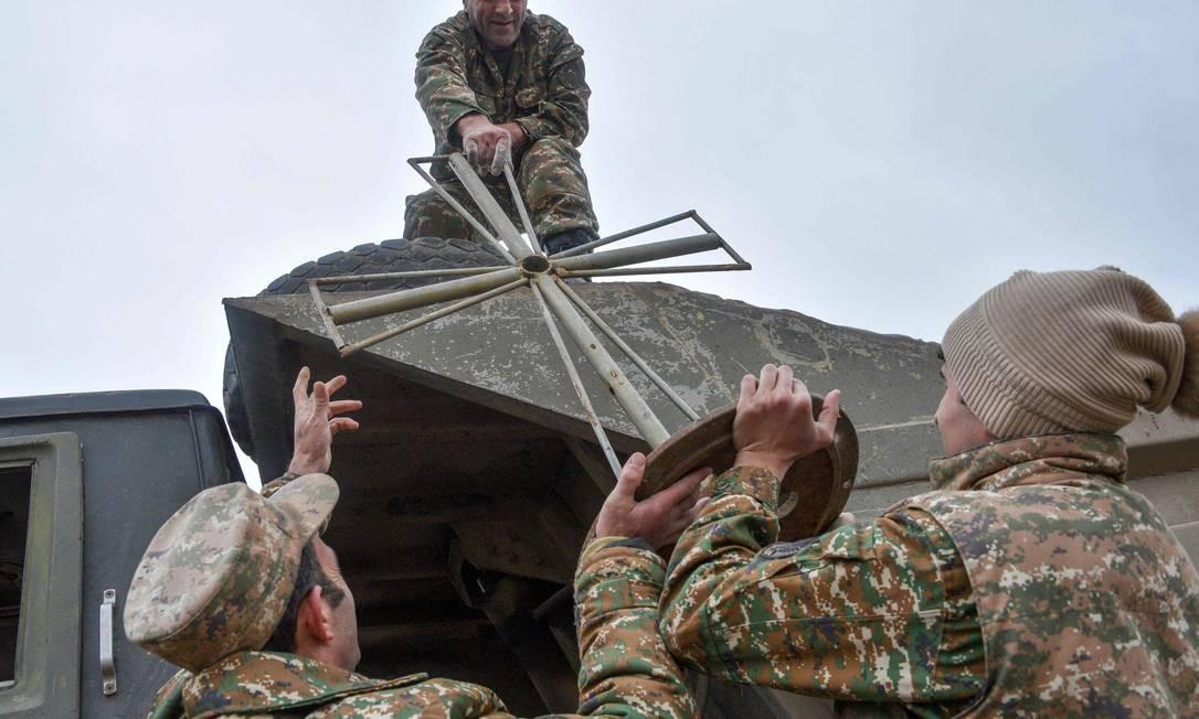 Soldados armênios seguram cruz enquanto evacuam quartel-general da cidade de Agdam, já que o território deve ser devolvido ao Azerbaijão, conforme estipulado em um acordo de paz mediado por Moscou Foto: KAREN MINASYAN / AFP