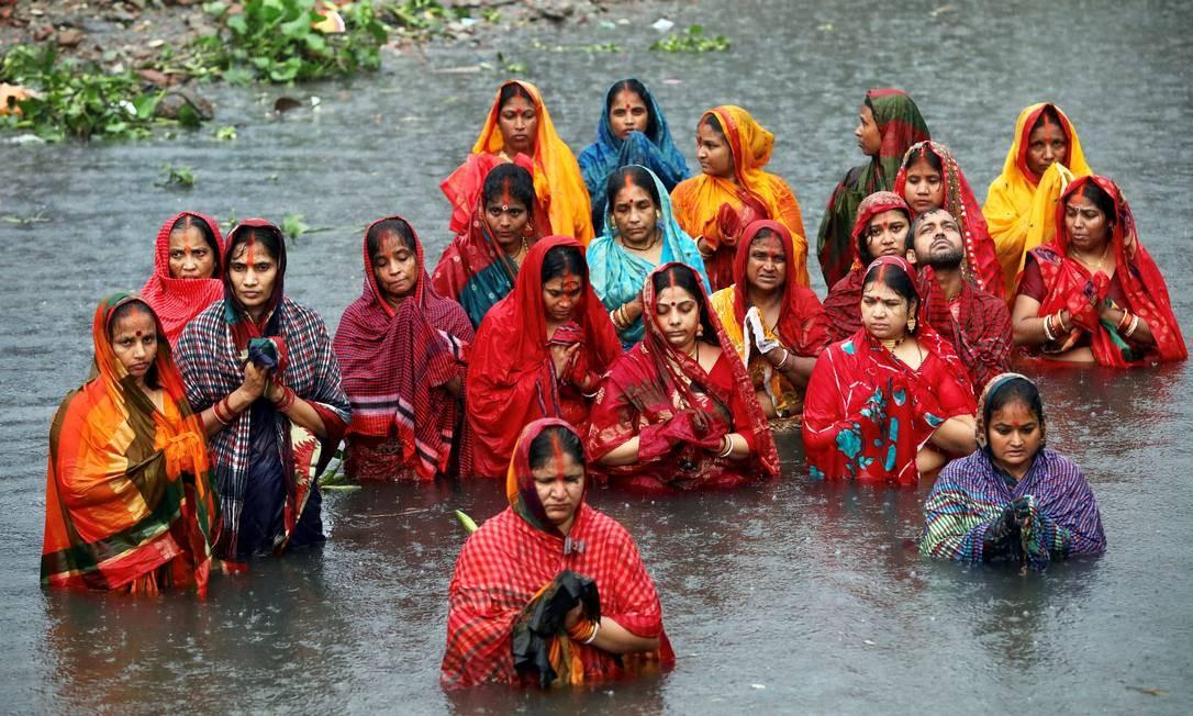 Devotos hindus ficam nas águas do rio Buriganga durante a chuva enquanto observam o festival Chhath Puja, em Dhaka, Bangladesh Foto: MOHAMMAD PONIR HOSSAIN / REUTERS