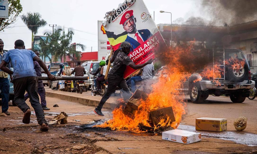 Aapoiador do músico ugandês que se tornou político Robert Kyagulanyi, também conhecido como Bobi Wine, carrega seu pôster enquanto protestam em uma rua contra a prisão de Kyagulanyi durante seu comício presidencial em Kampala, Uganda. Polícia ugandense disparou gás lacrimogêneo e balas de borracha contra grandes multidões de manifestantes que apoiavam o popular candidato à presidência Bobi Wine, que foi preso durante campanha, sob acusação de não respeitar medidas sanitárias devido à pandemia Foto: BADRU KATUMBA / AFP