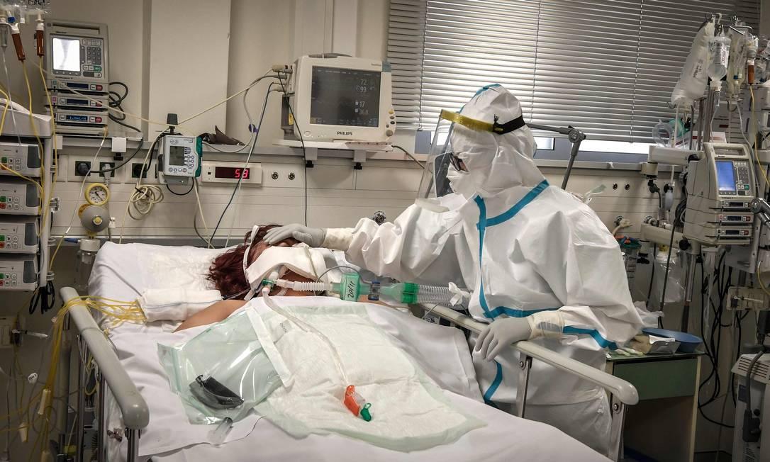 Enfermeira cuida de paciente na UTI, na Grécia Foto: LOUISA GOULIAMAKI/AFP / LOUISA GOULIAMAKI/AFP