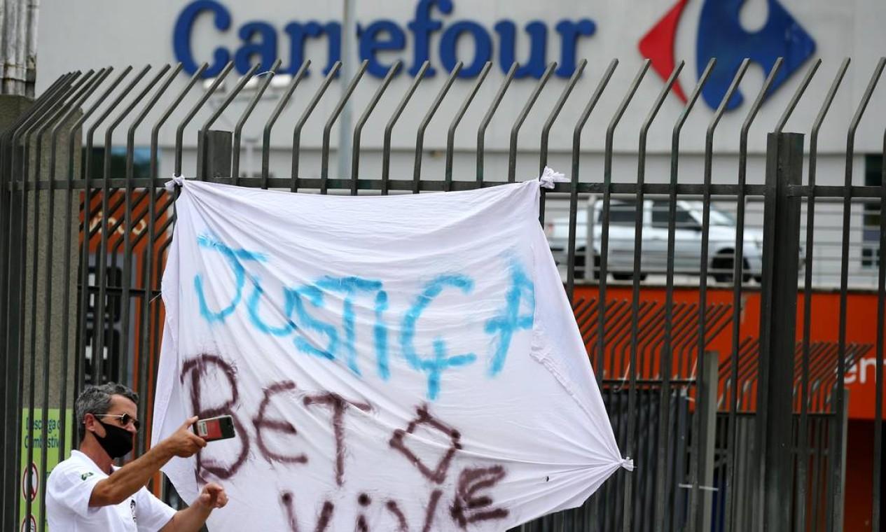Homem tira selfie em frente à cartaz pedindo justiça por Beto, homem negro assasinado brutalmente às vésperas do Dia da Consciência Negra Foto: DIEGO VARA / REUTERS