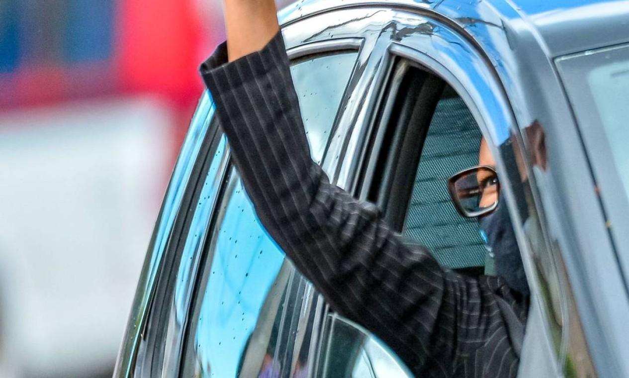 Mulher ergue o punho cerrado ao passar de carro pelo protesto no Carrefour Foto: SILVIO AVILA / AFP