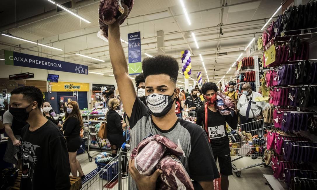 Manifestante ergue o punho segurando um pedaço de carne Foto: Guito Moreto / Agência O Globo