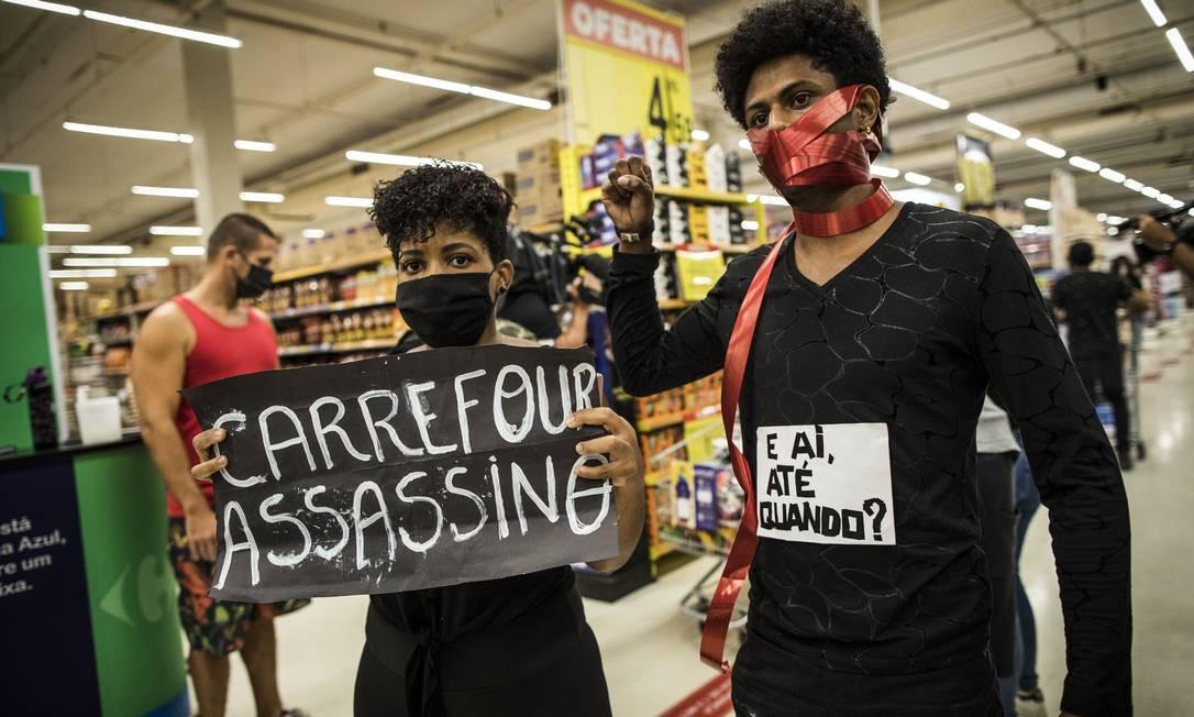 Manifestantes negros carregam cartazes Foto: Guito Moreto / Agência O Globo
