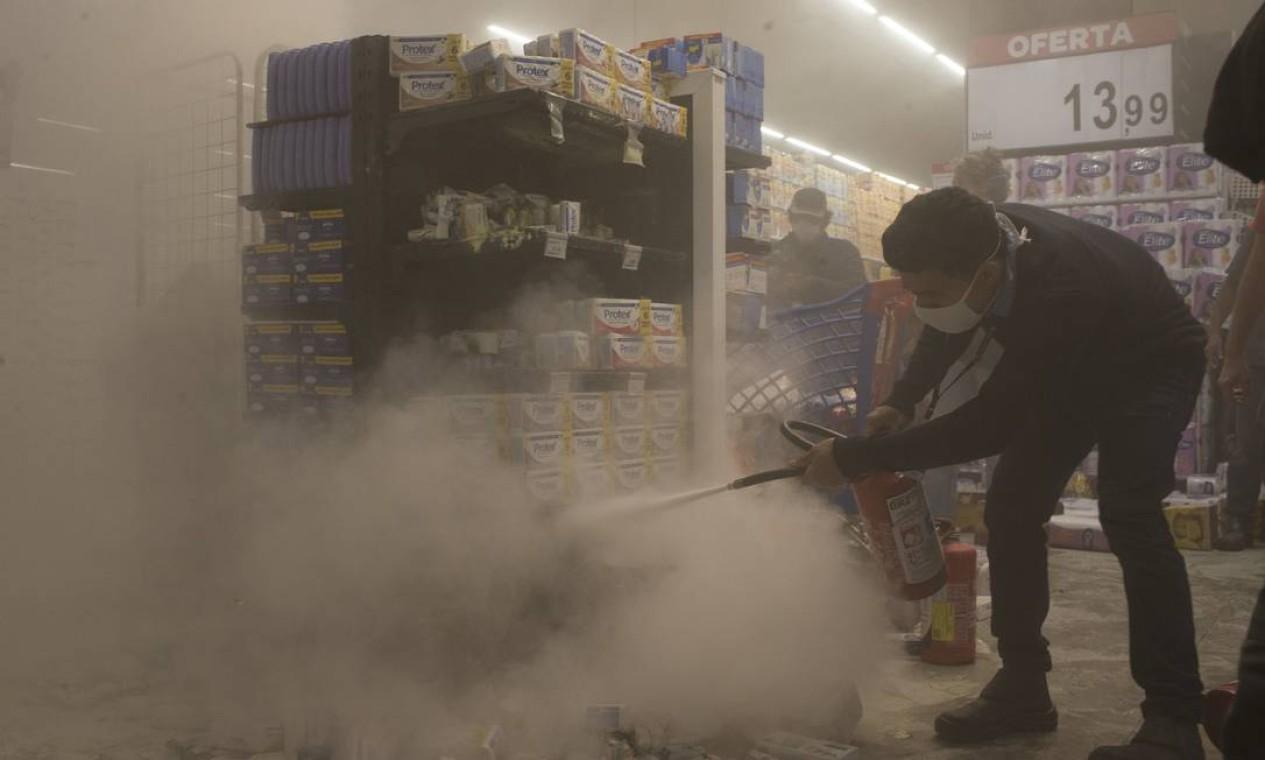 Funcionário apaga fogo de incêndio com extintor Foto: Edilson Dantas / Agência O Globo