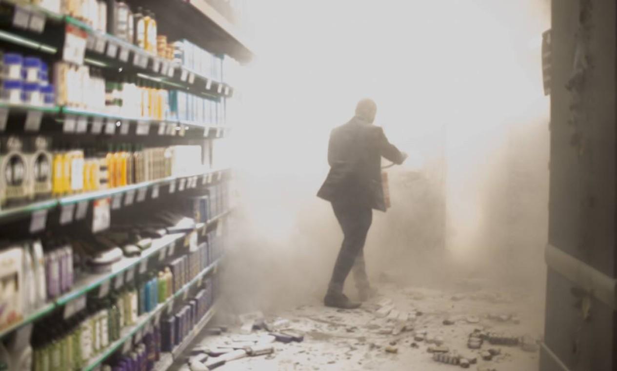Funcionário passa por fumaça em corredor que foi incendiado Foto: Edilson Dantas / Agência O Globo