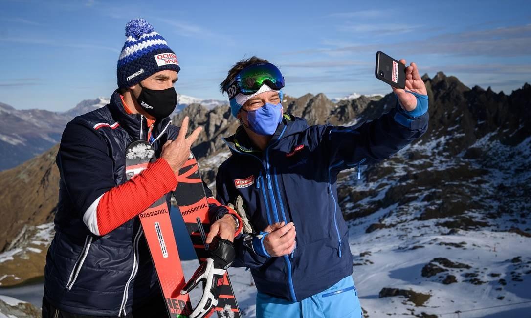 Usando máscaras, o ex-campeão olímpico de esqui Didier Defago, à esquerda, e o CEO da Televerbier, Laurent Vaucher, posam para uma selfie na estação de Verbier, nos Alpes suíços Foto: FABRICE COFFRINI / AFP