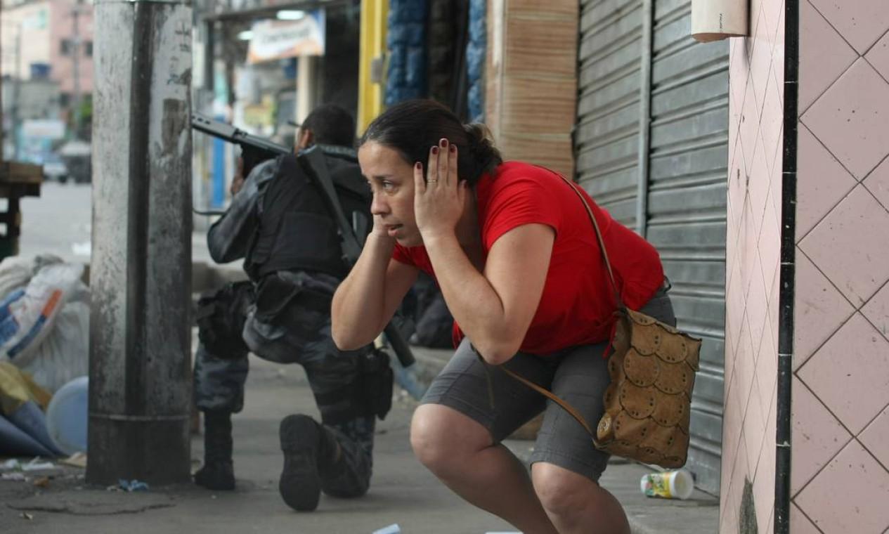 Abaixada, mulher tenta se protegor enquanto, ao lado dela, agente troca tiros com bandidos Foto: Marcelo Piu / Agência O Globo - 28/11/2020