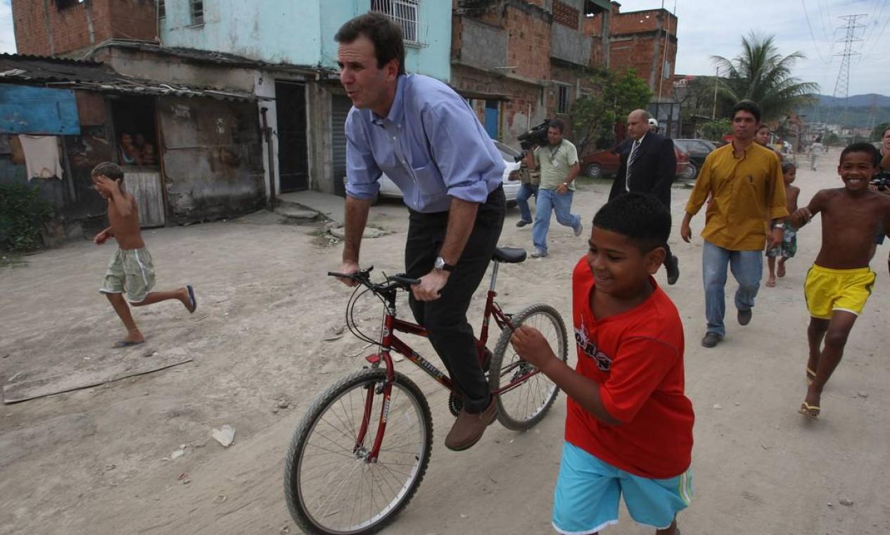 Em 2009, o então prefeito do Rio anda de bicicleta durante visita à comunidade de Vila Turismo, no Complexo do Alemão, Zona Norte Foto: Hipólito Pereira / Agência O Globo