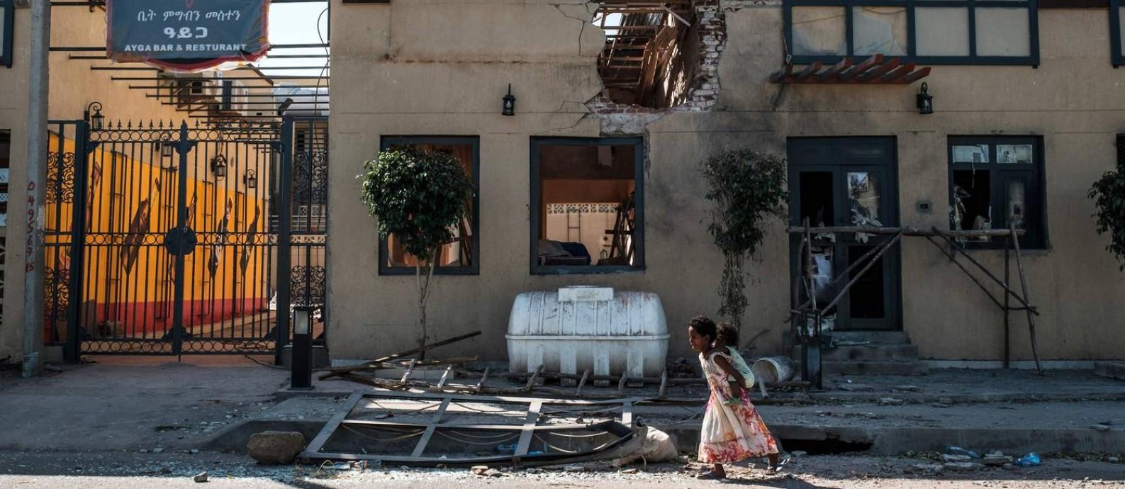 Crianças brincam em frente a um hotel bombardeado na cidade de Humera, na Etiópia Foto: Eduardo Soteras / AFP