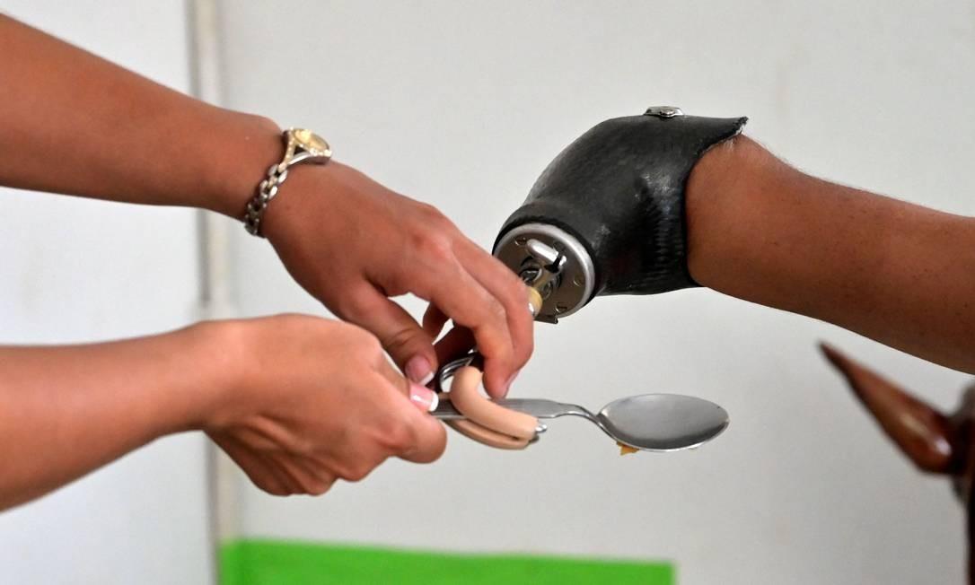 Mochoman recebe ajuda de sua esposa e treinadora Angie Garces para instalar talher na prótese Foto: RAUL ARBOLEDA / AFP