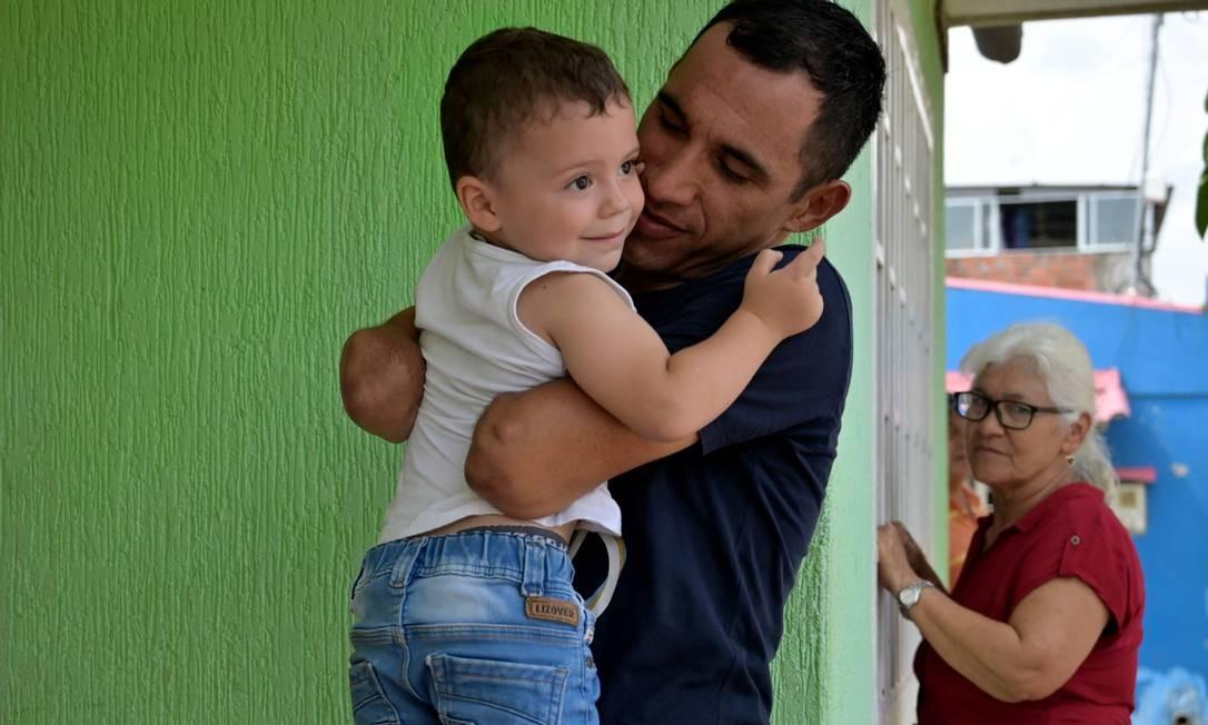 """Juan José Florián, o """"Mochoman"""", carrega seu filho Juan Jose enquanto sua mãe, algo do atentado com bomba que o mutilou, observa, em sua casa no município de Granada, Departamento de Meta, Colômbia Foto: RAUL ARBOLEDA / AFP"""