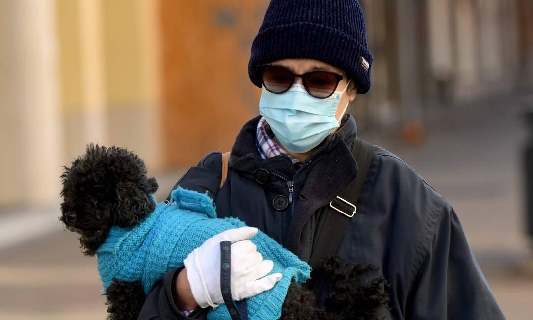 Mulher usando uma máscara protetora e luvas segura um cachorro enquanto caminha na Croácia, em meio à pandemia da Covid-19 Foto: DENIS LOVROVIC / AFP