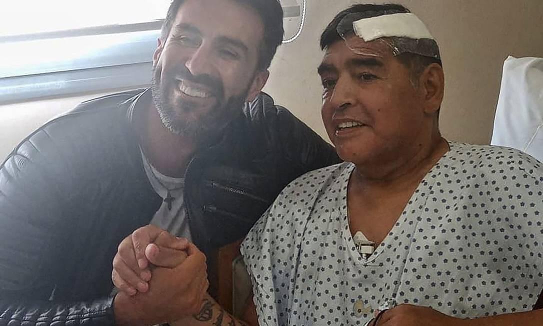 Diego Armando Maradona cumprimenta seu médico Leopoldo Luque em Olivos, após ser operado no início de novembro para remoção de um coágulo de sangue do cérebro. Foto: - / AFP