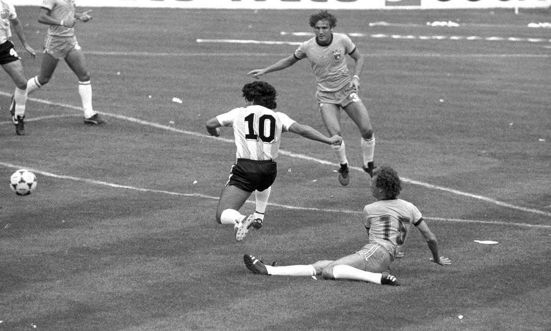 Maradona tenta ultrapassar o meia brasileiro Falcão na derrota por 3 a 1 para o Brasil, no Estádio do Sarriá, no Barcelona Foto: Erno Schneider / Agência O Globo - 07/02/1982