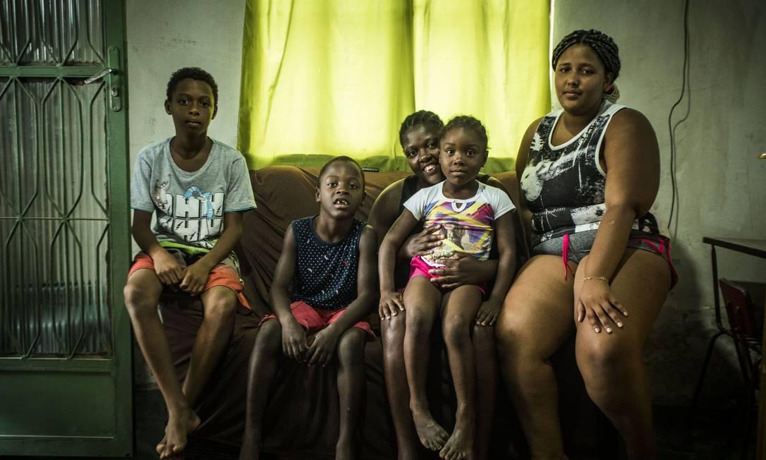 Lilia Siqueira e seus filhos contam com a ajuda não que não vem do dinheiro para completar a renda mensal da família Foto: Guito Moreto / Agência O Globo