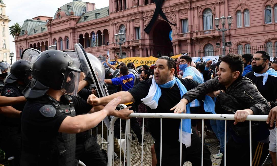 Torcedores de Diego Maradona discutem com a polícia para entrar na Casa Rosada, para velar o corpo de Maradona Foto: RONALDO SCHEMIDT / AFP
