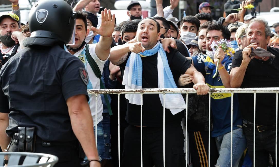 Torcedores de Diego Maradona discutem com a polícia para entrar na Casa Rosada, para velar o corpo de Maradona Foto: ALEJANDRO PAGNI / AFP