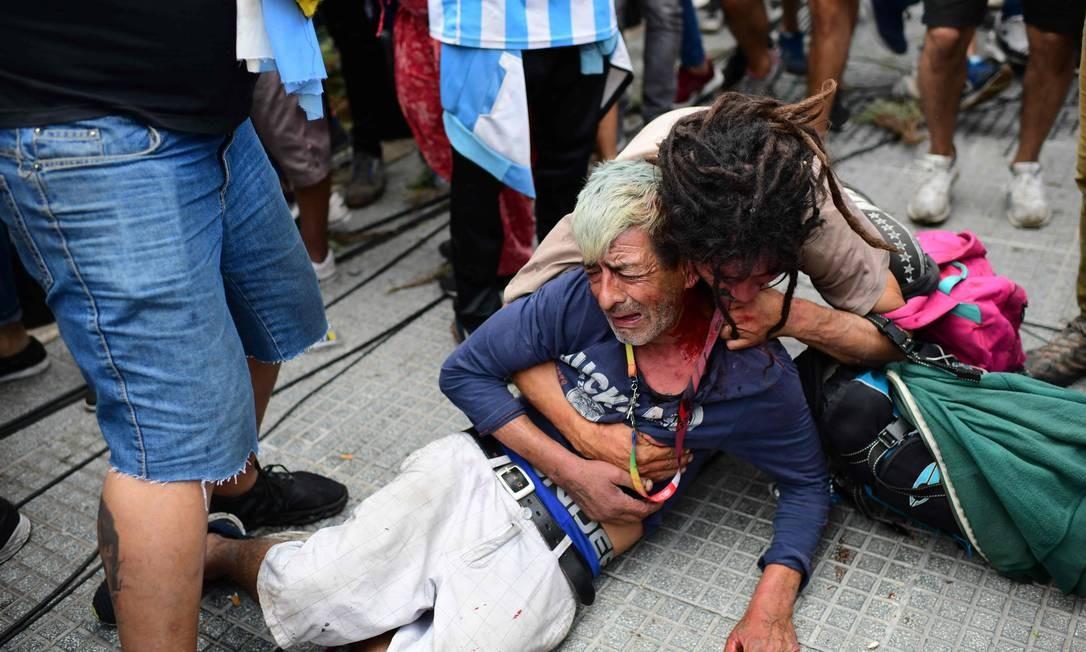 Fã chora após ser ferido durante brigas com a polícia enquanto esperava para entrar na Casa Rosada para homenagear a falecida lenda do futebol Diego Armando Maradona, em Buenos Aires Foto: RONALDO SCHEMIDT / AFP