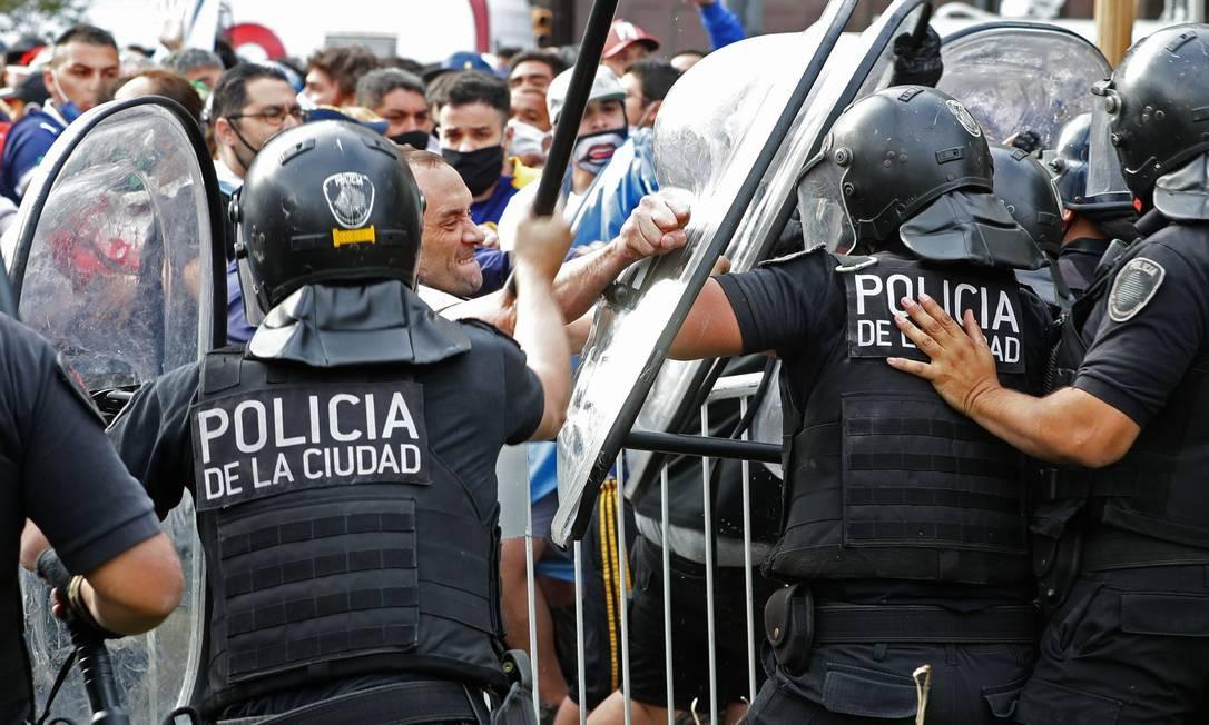 Fãs de Diego Maradona entram em conflito com policiais em frente à Casa Rosada, local do velório da lenda do futebol, que morreu nesta quarta-feira, em Buenos Aires, Argentina Foto: ALEJANDRO PAGNI / AFP