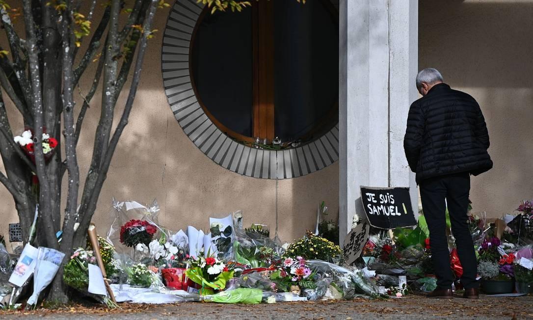 Homem olha para homenagens deixadas ao professor Samuel Paty, morto em outubro, em frente a escola em Conflans-Sainte-Honorine Foto: ANNE-CHRISTINE POUJOULAT / AFP