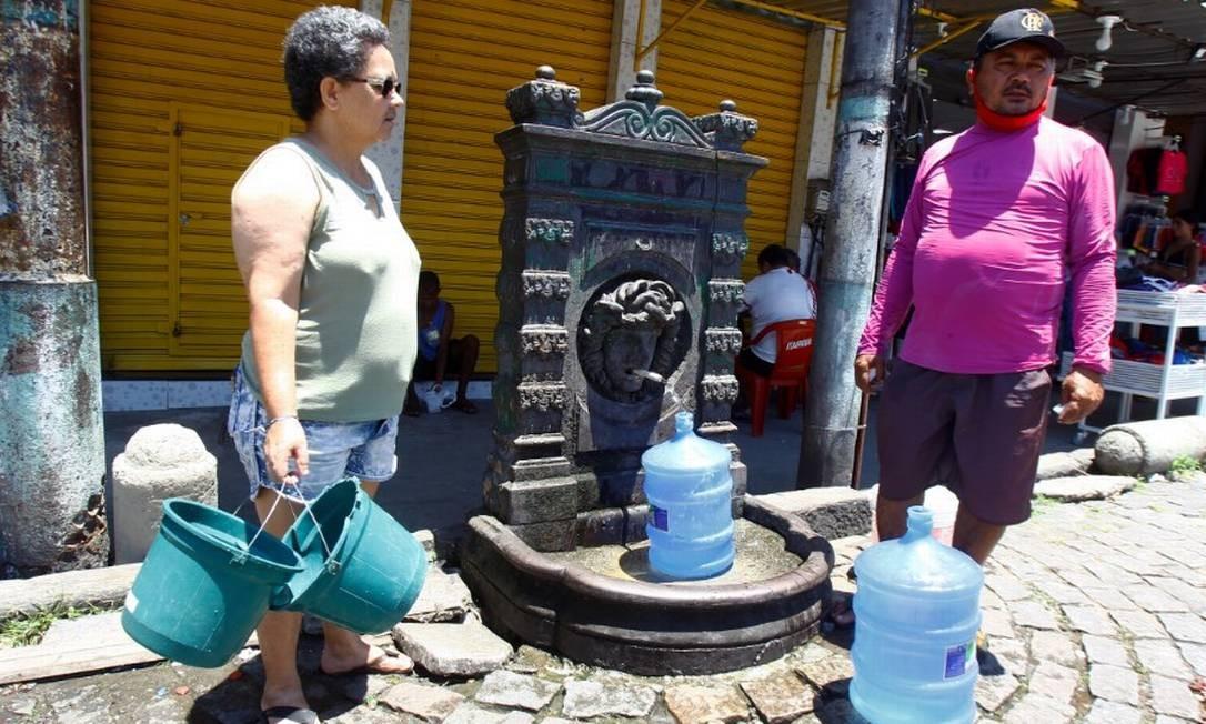 Eva Maria de Carvalho e João Vicente recorrem à fonte para conseguir água Foto: Guilherme Pinto / Agência O Globo