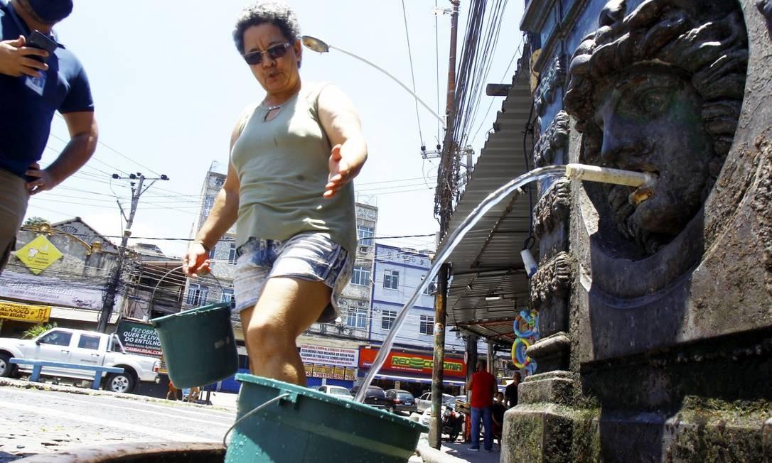 A dona de casa Eva Maria busca água em uma fonte no Largo do Pedregulho, em Benfica, após caminhar quase meio quilômetro Foto: Guilherme Pinto / Agência O Globo