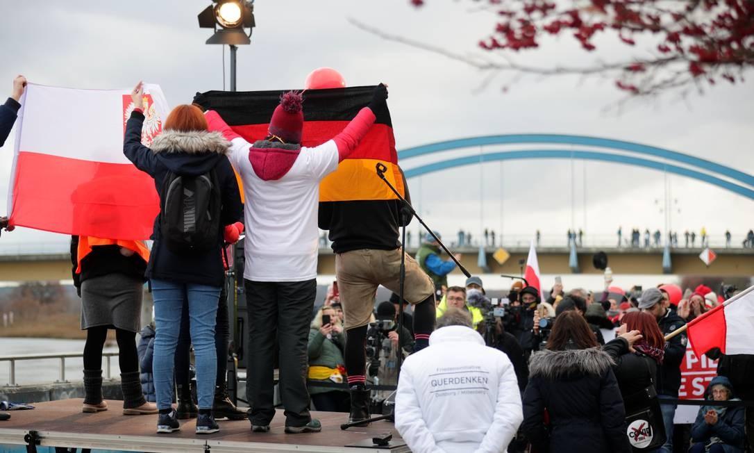 Negacionistas polonêses e alemães participam de um protesto contra as restrições do governo para conter a segunda onda da Covid-19 na fronteira em Frankfurt do Óder, Alemanha Foto: HANNIBAL HANSCHKE / REUTERS