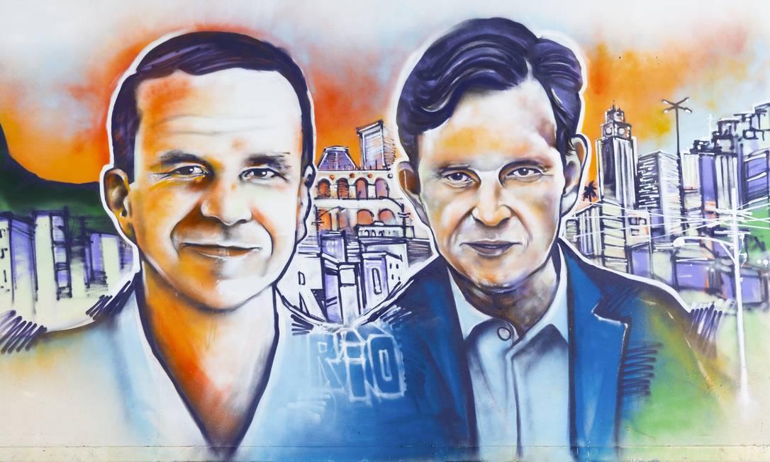 Painel pintado pelo artista urbano Ment retrata os candidatos à Prefeitura do Rio Eduardo Paes e Marcelo Crivella Foto: Arte de Marcelo Ment/Foto de Leo Martins