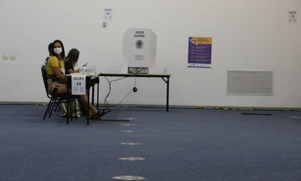 Mesários aguardam eleitores. No chão, marcas para que se mantenha distanciamento durante eventual fila Foto: Fabiano Rocha / Agência O Globo
