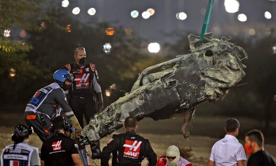 A célula de sobrevivência do carro do piloto francês Romain Grosjean da Haas F1 é removida após um acidente durante logo na largada do GP do Bahrein Foto: TOLGA BOZOGLU / AFP