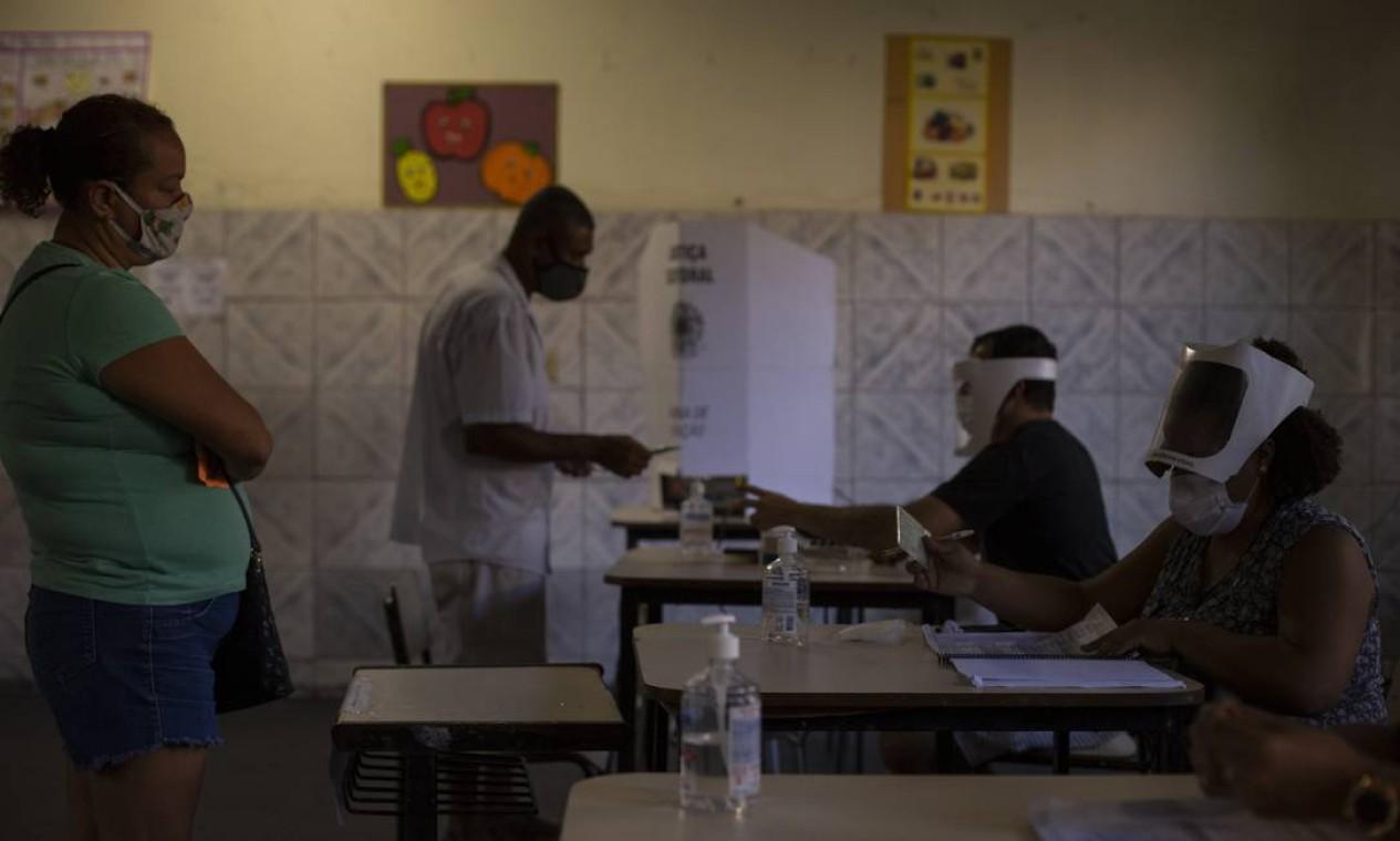 Mesários usam escudo facial para atender eleitores na Escola Municipal Ubaldo de Oliveira, Bangu, Zona Oeste Foto: Gabriel Monteiro / Agência O Globo