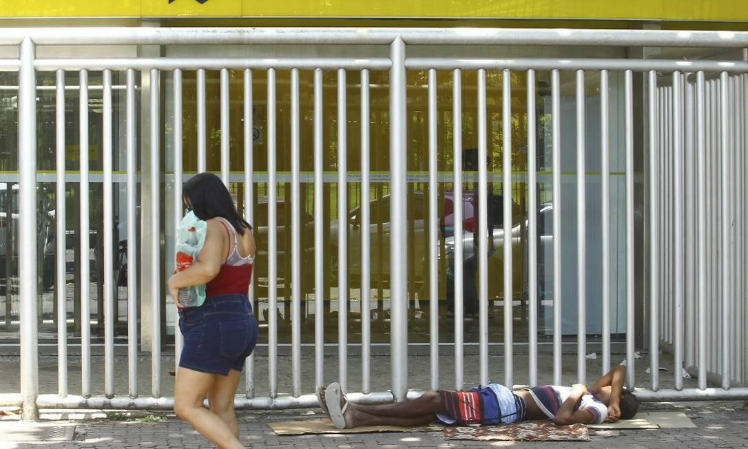Mulher passa em frente a rapaz que dorme junto a prédio em Ipanema: censo de população de rua, prometido há anos, só deve ser divulgado este mês Foto: Guilherme Pinto / Agência O Globo