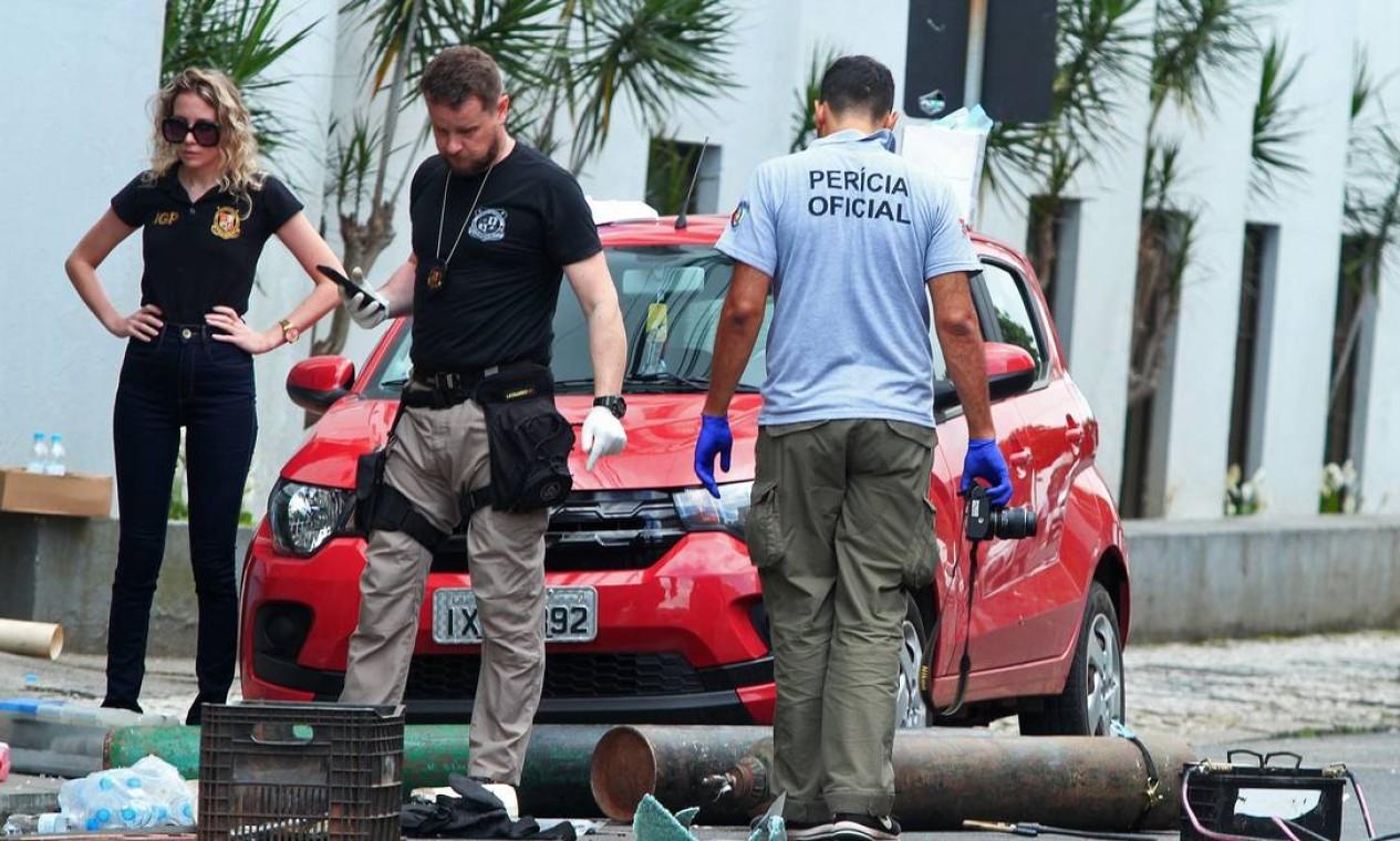 Polícia examina equipamentos suspeitos de serem usados para fazer explosivos na cena de um assalto a banco em Criciúma Foto: GUILHERME HAUN / AFP