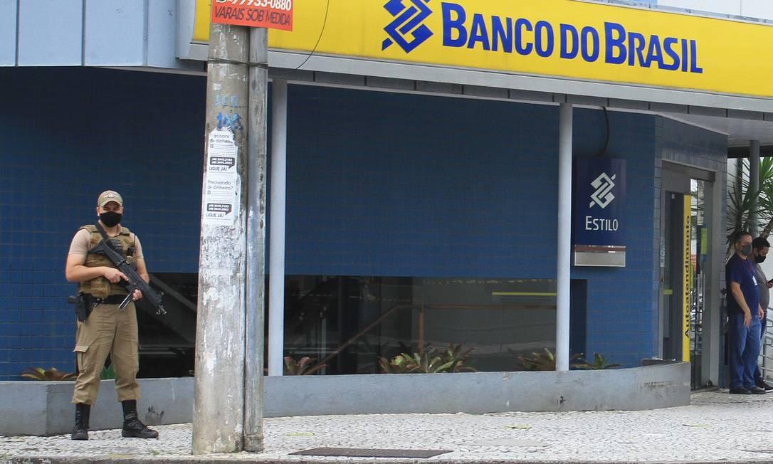 Policial faz a segurança de agência do Banco do Brasil em Criciúma assaltada por bando de pelo menos 30 criminosos Foto: GUILHERME HAUN / AFP