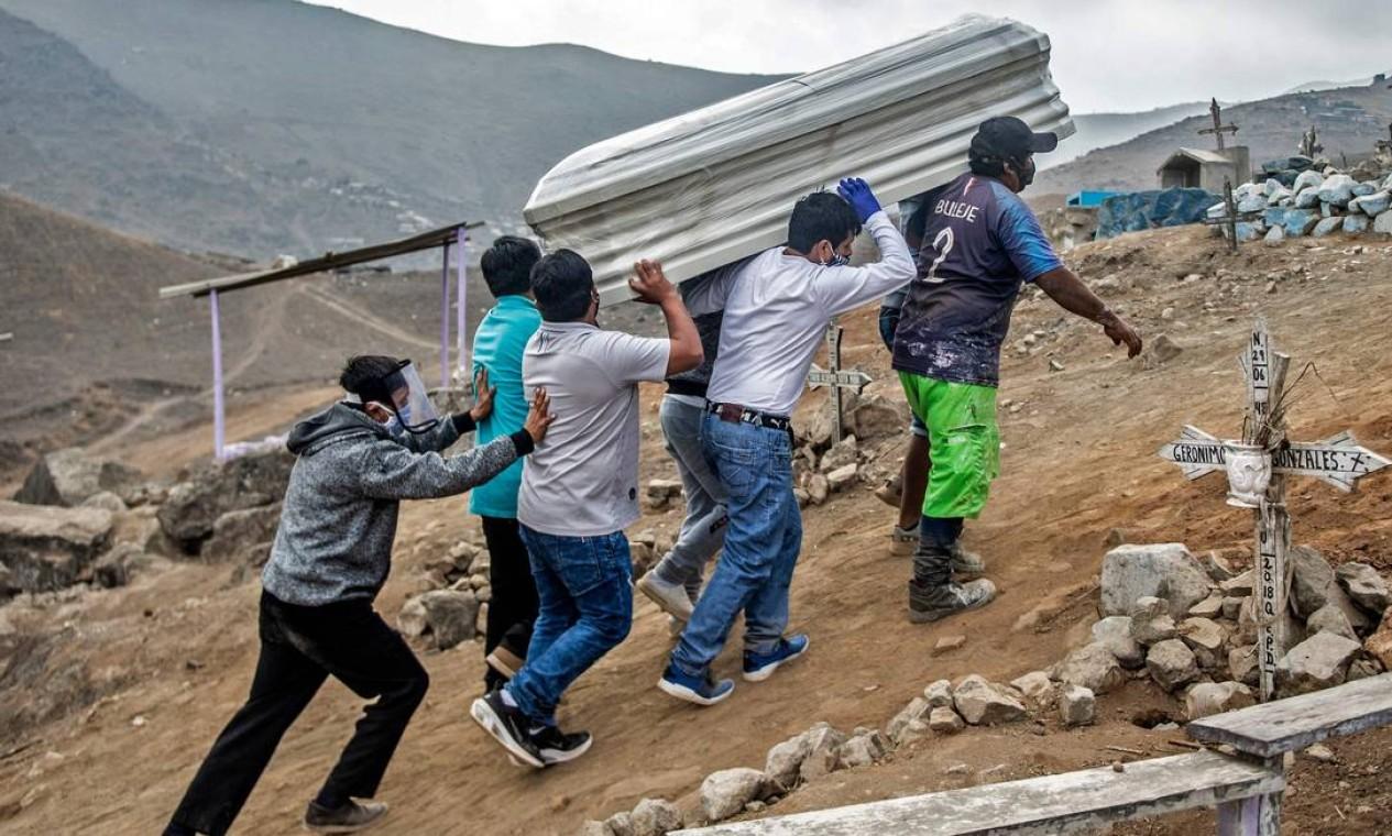Parentes carregam o caixão de uma suposta vítima de COVID-19 no cemitério Nueva Esperanza, um dos maiores da América Latina, na periferia sul de Lima, no Peru. Foto: ERNESTO BENAVIDES / AFP