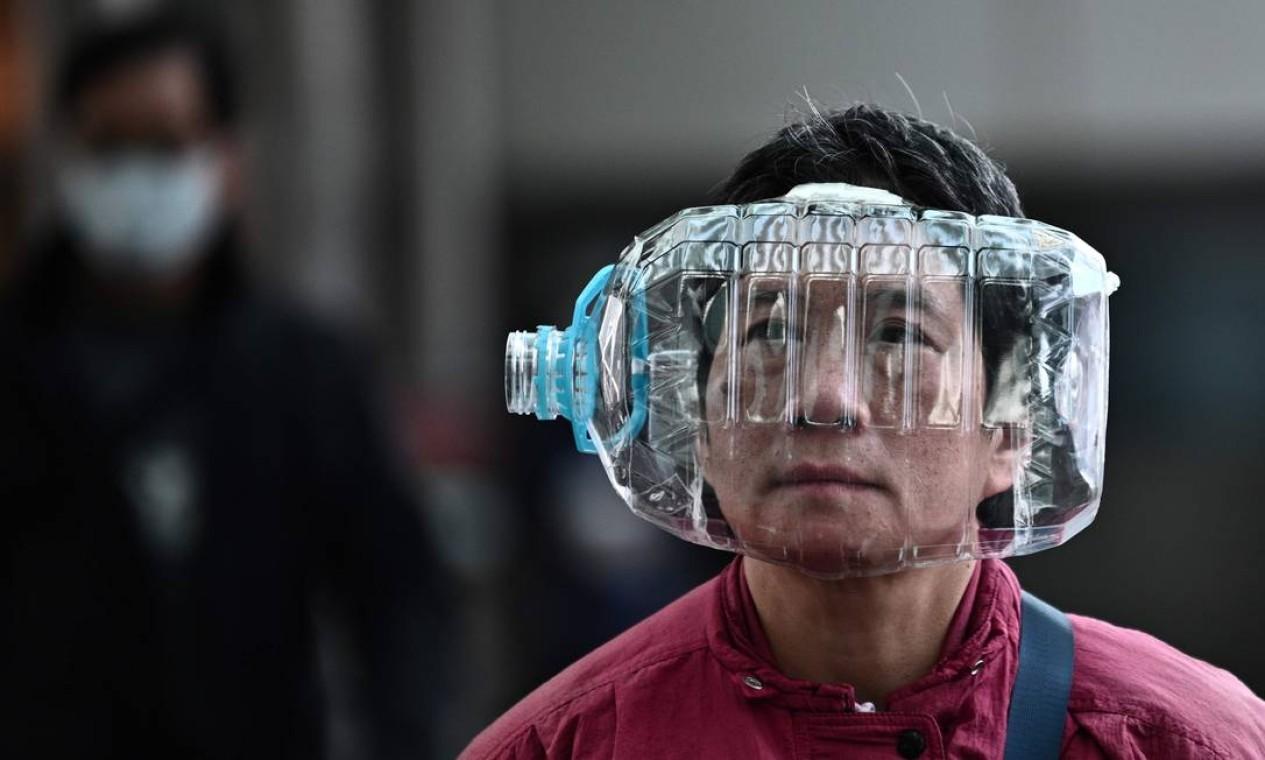 Galão de água de plástico com um recorte é usado para cobrir o rosto, enquanto caminha em uma passarela, em Hong Kong. Em janeiro, a Covid-19 já tinha matado 170 pessoas na China, mas a Organização Mundial da Saúde (OMS) ainda estava cautelosa em declarar emergência global Foto: ANTHONY WALLACE / AFP - 31/01/2020