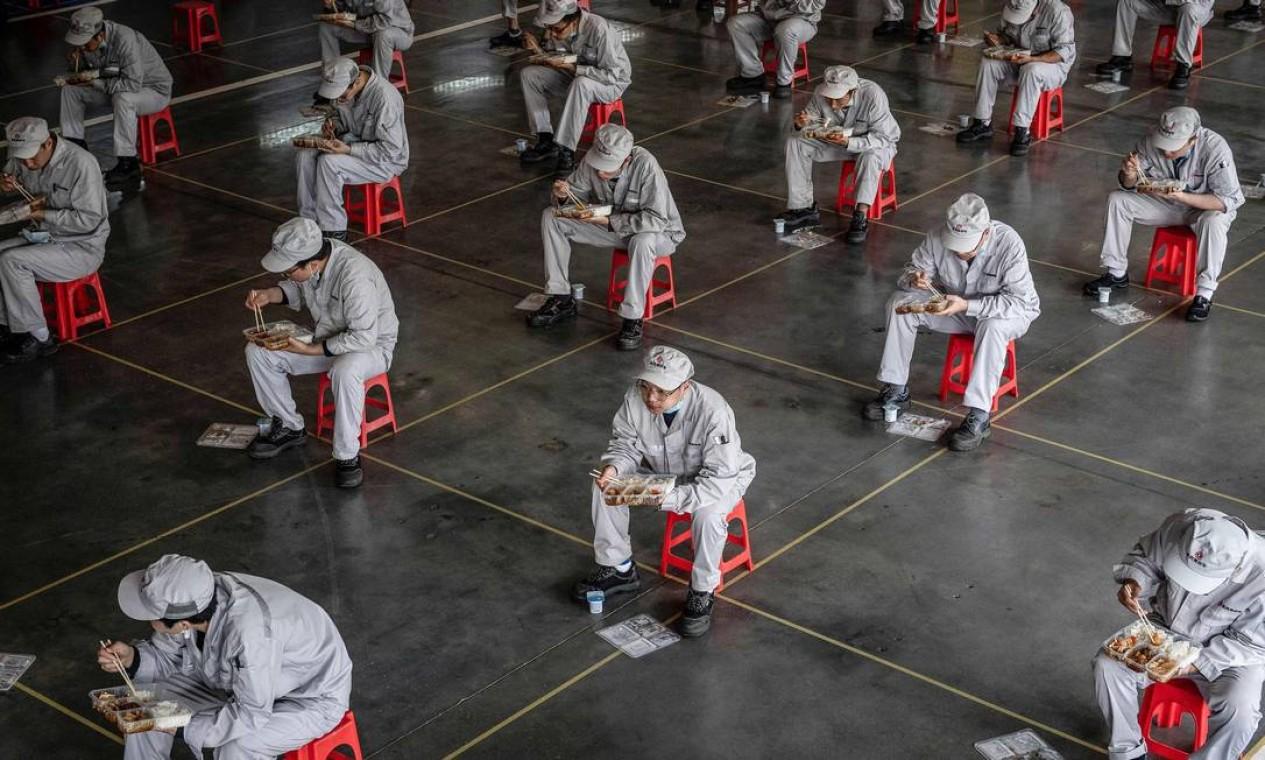Funcionários comendo durante o intervalo para o almoço em uma fábrica de automóveis da Dongfeng Honda, em Wuhan, na província de Hubei, na China central, onde o coronavírus COVID-19 foi detectado pela primeira vez. Com medidas eficazes de combate à pandemia, o país que alertou o mundo sobre o perigo, retomou a rotina deopis de dois meses de bloqueio Foto: STR / AFP - 23/03/2020