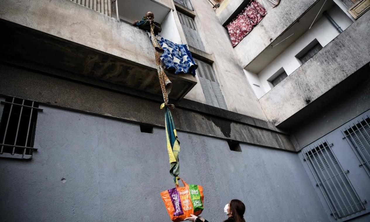 Morador do condomínio Maison Blanche, composto por 226 moradias em sua maioria insalubres, recebe alimentos oferecidos por vizinhos, usando uma corda confeccionada com cobertores, em Marselha, sul da França, no décimo quinto dia de bloqueio com o objetivo de conter a disseminação do novo coronavírus Foto: ANNE-CHRISTINE POUJOULAT / AFP - 31/03/2020