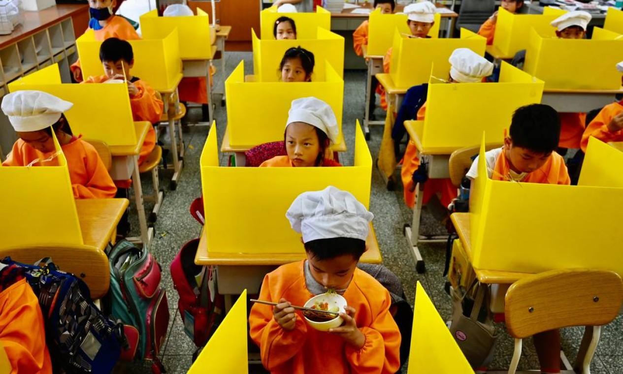 Alunos almoçam em carteiras com divisórias de plástico como medida preventiva para conter a disseminação do coronavírus, na Dajia Elementary School, em Taipei, capital de Taiwan Foto: SAM YEH / AFP - 29/04/2020