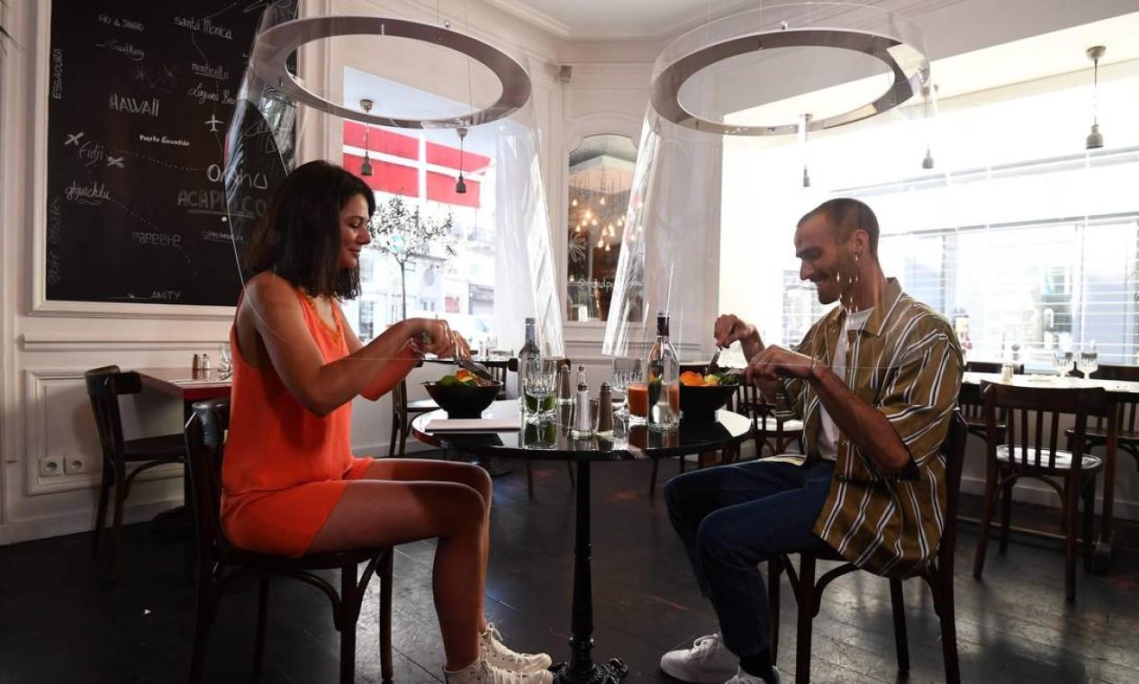 Casal almoça sob proteção de plexiglass projetado por Christophe Gernigon no restaurante H.A.N.D, em Paris, enquanto a França facilitava as medidas de bloqueio tomadas para conter a propagação da primeira onda da pandemia Foto: ALAIN JOCARD / AFP - 27/05/2020