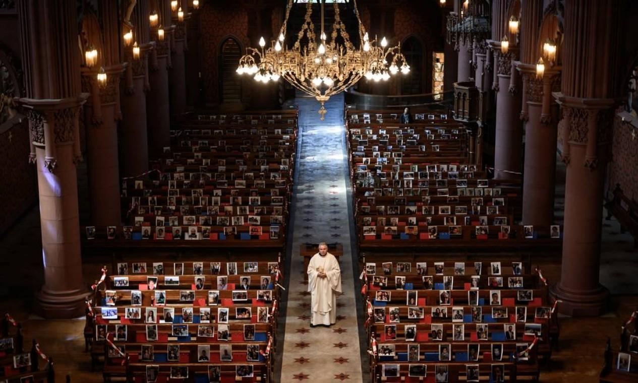 O abade Vincent Marville fica no corredor central da Basílica de Neuchatel, que exibe os retratos de 400 paroquianos que não puderam comparecer à missa devido ao surto da COVID-19. A Suíça começou a aliviar as restrições impostas para controlar a pandemia COVID-19, mas missas estavam proibidas Foto: FABRICE COFFRINI / AFP - 03/05/2020