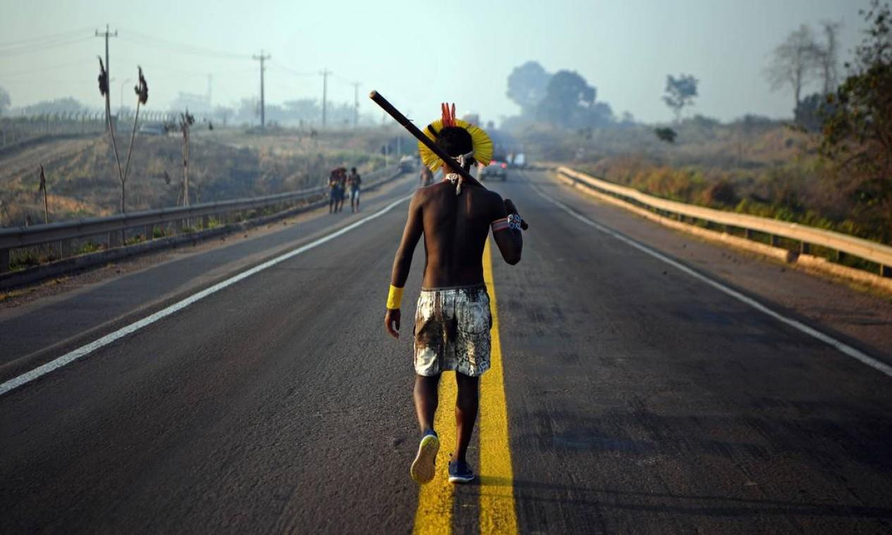 Membro da tribo Kayapó caminha ao longo da rodovia BR-163 durante um protesto em Novo Progresso, no estado do Pará. Manifestantes indígenas bloquearam trecho importante da rodovia transamazônica para protestar contra a falta de apoio governamental durante a pandemia do coronavírus e desmatamento ilegal dentro e ao redor de seus territórios Foto: CARL DE SOUZA / AFP