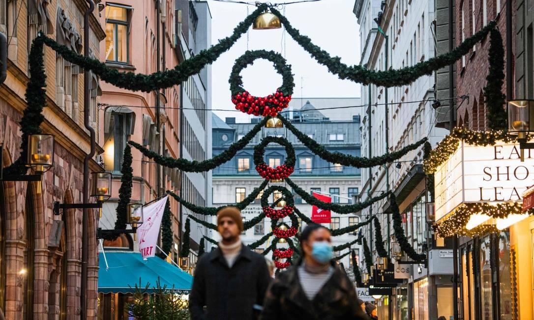 Pedestres caminham em rua com decorações de Natal em Estocolmo, na Suecia Foto: JONATHAN NACKSTRAND / AFP / 3-12-2020