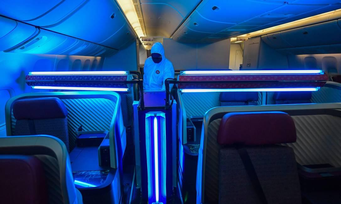 No escuro. Funcionário da Latam usa luz ultravioleta para limpar interior de avião: alta nas infecções eleva incertezas Foto: NELSON ALMEIDA / AFP