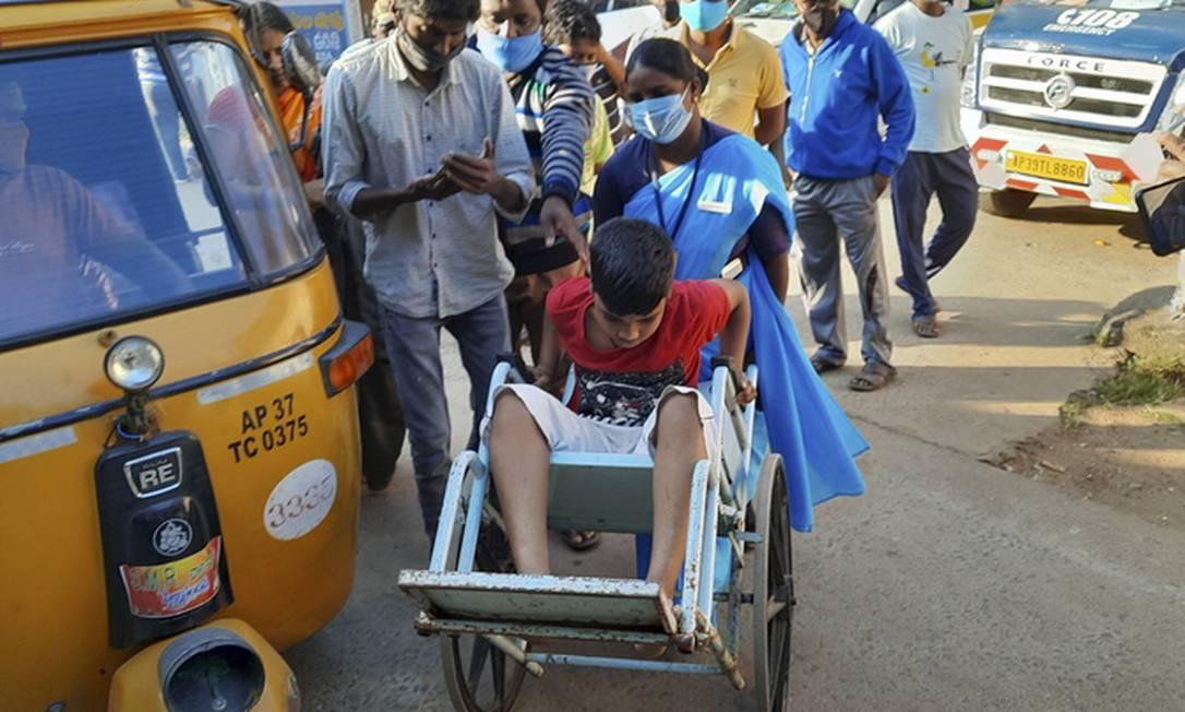 Jovem paciente é levado ao hospital de Eluru em cadeira de rodas Foto: AP