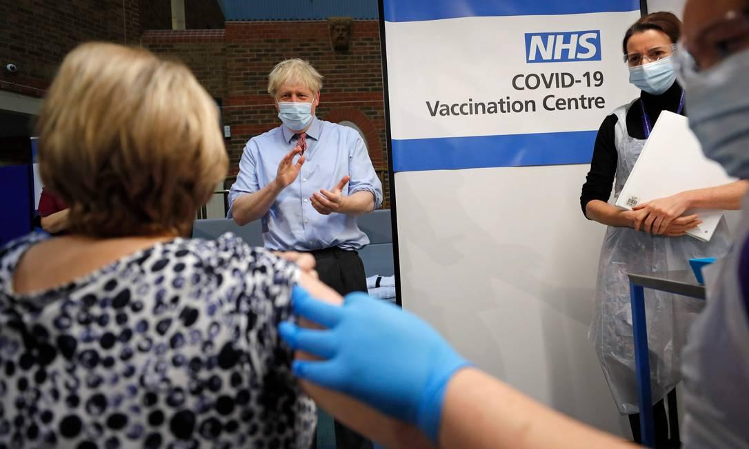 O primeiro-ministro da Grã-Bretanha, Boris Johnson, aplaude depois que a enfermeira Rebecca Cathersides administrou a vacina da Pfizer, laboratório dos EUA, desenvolvida em parceria com o alemão BioNTech, em Lyn Wheeler no Guy's Hospital em Londres Foto: FRANK AUGSTEIN / AFP